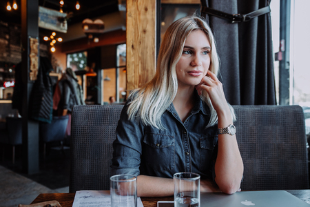 beautiful young woman sitting at table with laptop and looking at window in cafe