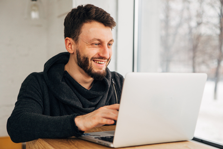 Happy young bearded student keeping his hands on keyboard of generic laptop computer while working on diploma project