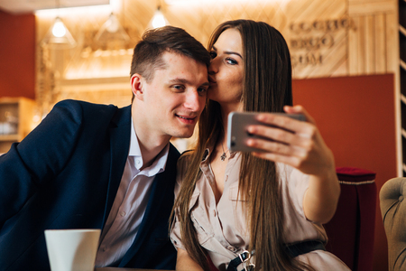 Happy young couple taking selfie with smart phone at cafe