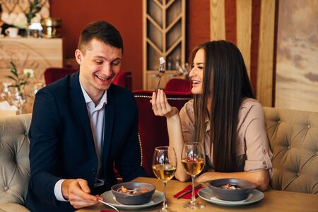 happy couple having dinner at restaurant and laughing
