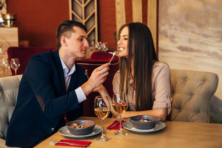 a man feeds his woman in a restaurant