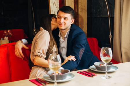 a young girl in the restaurant kissing her boyfriend Standard-Bild