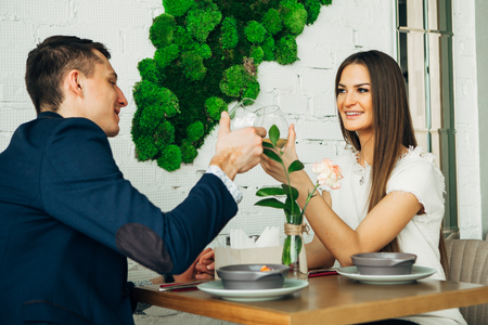 smiling couple having dinner and drinking white wine at date in restaurant