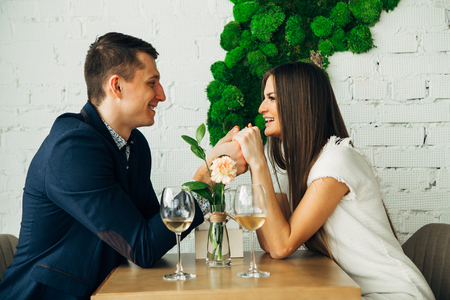 Cheerful young man and woman are dating in restaurant. They are sitting at the table and looking at each other with love. Standard-Bild