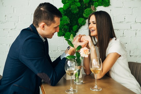 Cheerful young man and woman are dating in restaurant. They are sitting at the table and looking at each other with love. Zdjęcie Seryjne