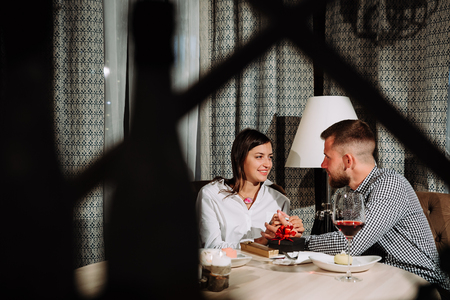 the man gave his girlfriend a gift for Valentine's day and holds her hands,Young happy couple romantic date drink glass of red wine at restaurant, celebrating valentine day Standard-Bild
