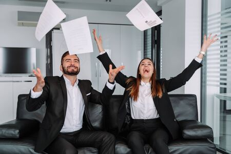 Two handsome cheerful business people celebration successful with throwing paper in workplace. Zdjęcie Seryjne