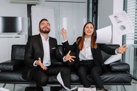 happy colleagues throwing business papers in modern office