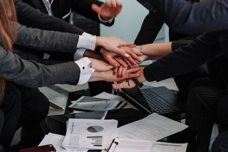 diverse workers or employees put hands in stack showing support and unity, reach shared goal together, people engaged in teambuilding activity or training. Teamwork concept