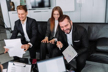 a group of workers sitting at a table in a conference room laugh and share ideas about a new project with their colleagues Zdjęcie Seryjne
