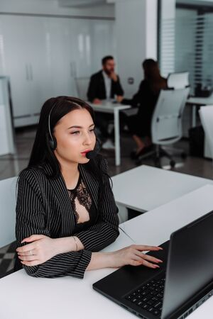 Call center. Focus on the beautiful woman in the headset