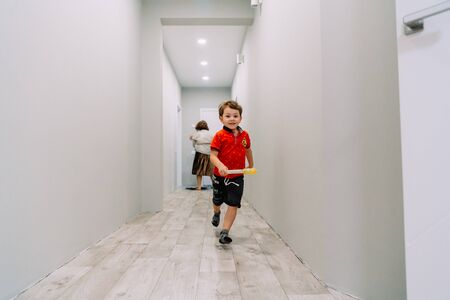 the boy runs down the hall of the house