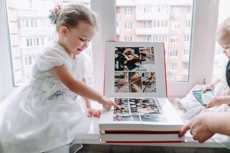 a little girl looks at an album of photos