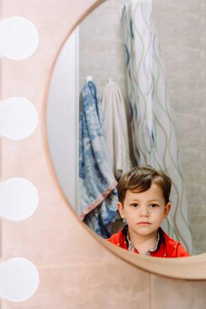 sad boy looks in the bathroom mirror
