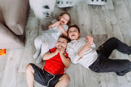 Cute little children having fun, lying on the floor in kindergarten Zdjęcie Seryjne