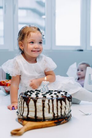 a little girl in a dress is preparing to blow out a candle on a birthday cake