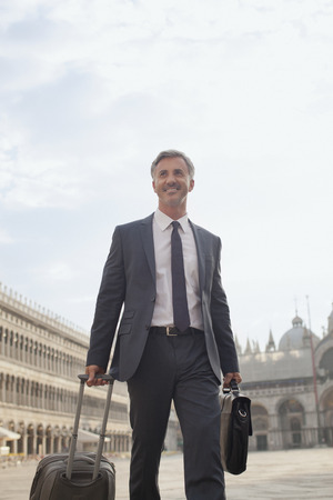 st  mark's: Smiling businessman pulling suitcase through Saint Marks Square in Venice LANG_EVOIMAGES