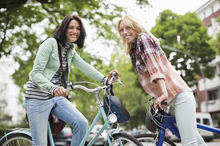 transportation: Women sitting on bicycles on city street