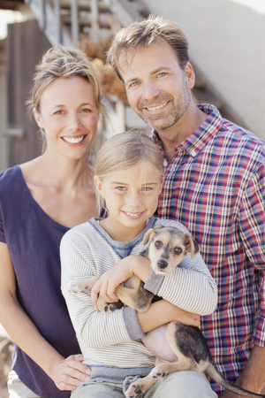 family: Portrait of smiling family holding puppy