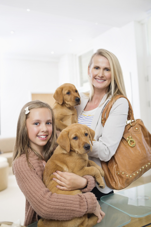 Mother and daughter holding dogs in vets surgery