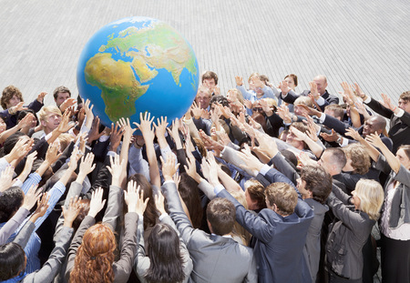 Crowd of business people reaching for globe