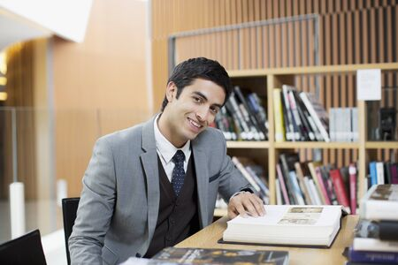 business: Portrait of smiling businessman reading book in library