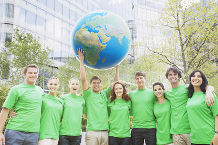Portrait of team in green t-shirts lifting globe overhead
