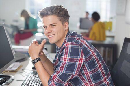 technology: Businessman smiling at desk LANG_EVOIMAGES