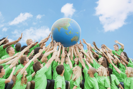 Team in green t-shirts lifting globe overhead LANG_EVOIMAGES