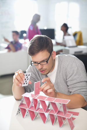 jamaican man: Businessman making house of cards in office
