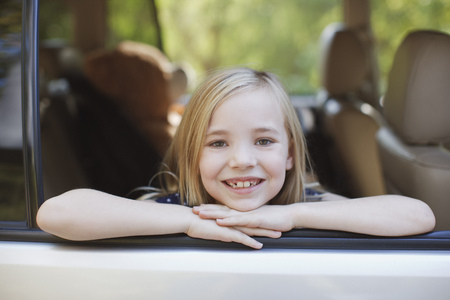 looking away from camera: Smiling girl leaning out car window LANG_EVOIMAGES