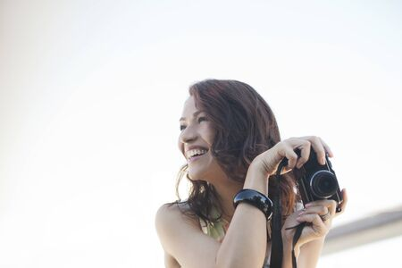 looking away from camera: Smiling woman taking pictures outdoors LANG_EVOIMAGES