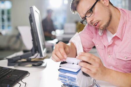 rolodex: Businessman searching for address on desk LANG_EVOIMAGES