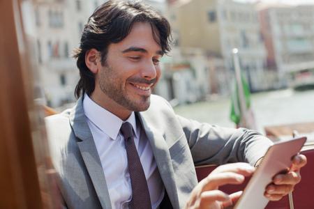 Smiling businessman using digital tablet on boat in Venice