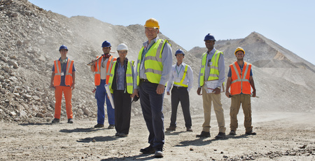Business people and workers standing in quarry