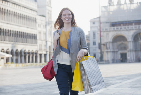 Smiling woman carrying shopping bags through St. Mark's Square in Venice