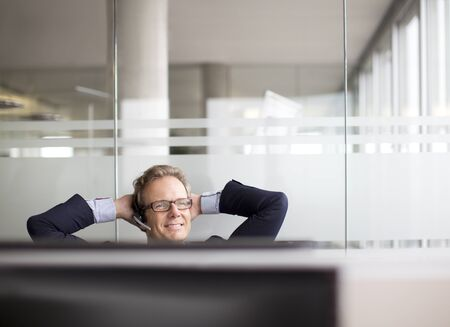 arms behind head: Businessman talking on headset in office