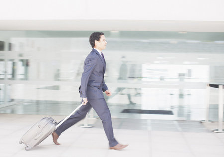 Businessman with suitcase rushing along airport corridor