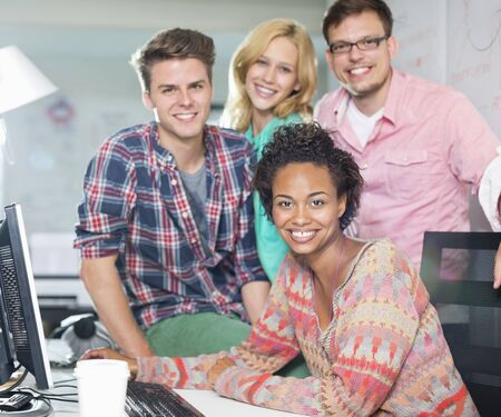 jamaican man: Business people smiling at desk LANG_EVOIMAGES