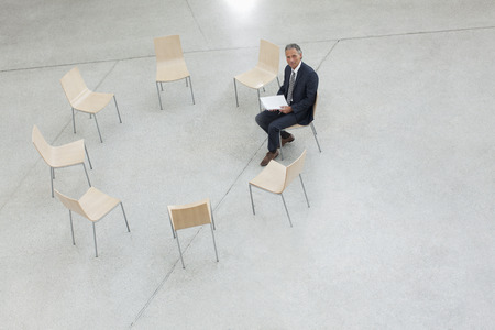 round chairs: Portrait of smiling businessman sitting in circle of chairs