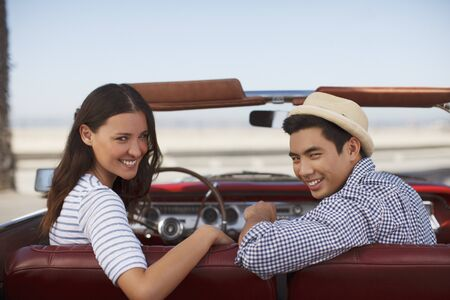 looking away from camera: Smiling couple sitting in convertible