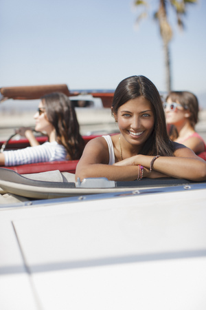 looking away from camera: Smiling woman sitting in convertible