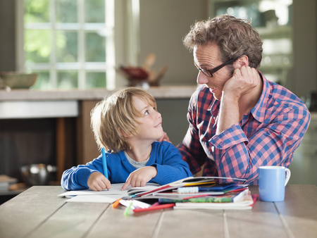 Father and son doing homework at kitchen table
