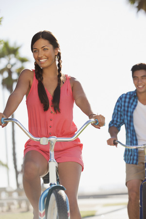 transportation: Smiling couple riding bicycles together
