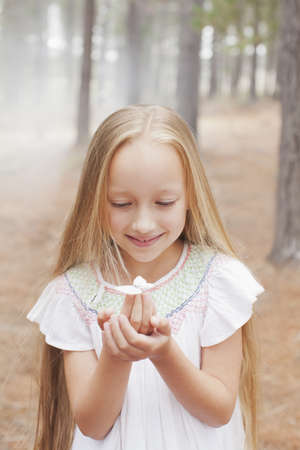 waist down: Close up of girl holding butterfly in woods
