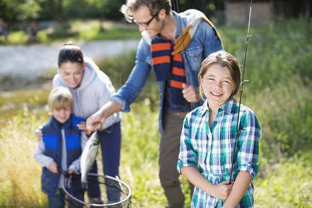 admiring: Family admiring fishing catch outdoors