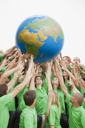 Team in green t-shirts reaching for globe overhead