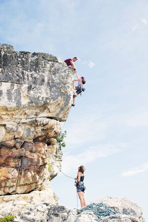 scaling: Climbers scaling steep rock face LANG_EVOIMAGES