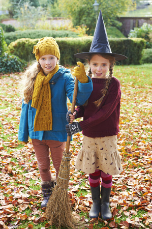 Girls playing with witchs hat and broom outdoors