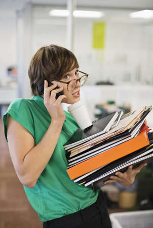Businesswoman with folders talking on cell phone